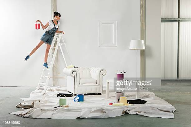 young woman decorating room - step ladder stock photos and pictures