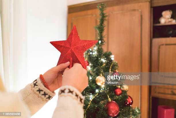 young woman decorating the christmas tree - christmas star stock photos and pictures