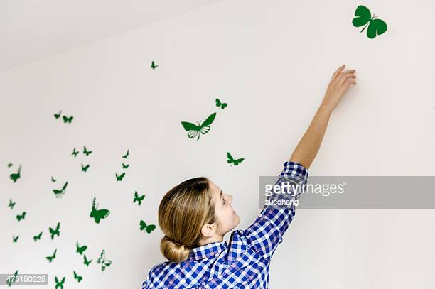 Young woman decorating wall with green butterflies