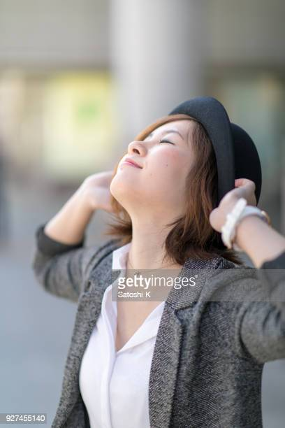 Young woman deep breathing in city