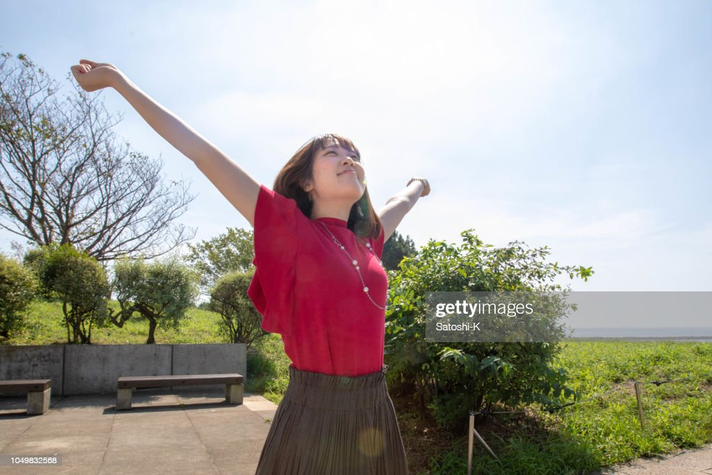 Young woman deep breathing under the sun : Stock Photo