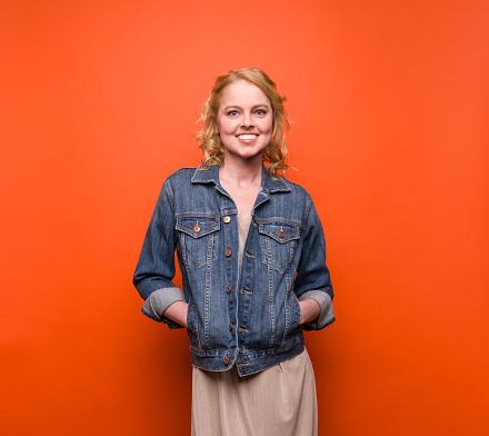 Young woman, denim jacket on orange background - gettyimageskorea