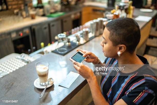 young woman depositing check by phone in the cafe - bank deposit slip stock pictures, royalty-free photos & images