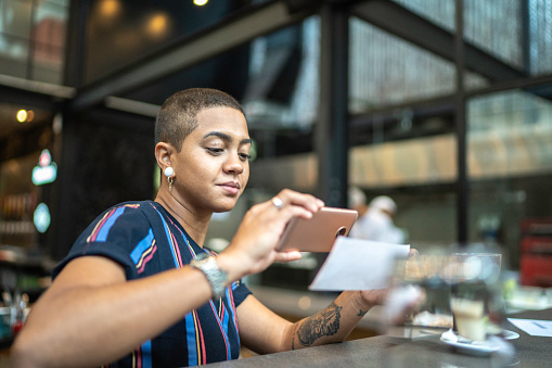 Young woman depositing check by phone in the cafe 1155418578