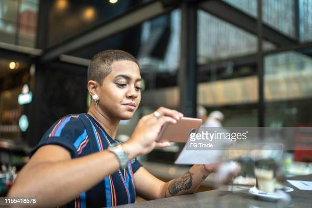 young woman depositing check by phone in the cafe - financial bill stock pictures, royalty-free photos & images