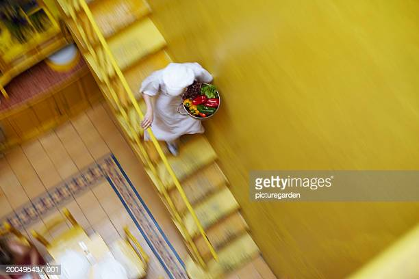 Young woman descending stairs in restaurant (blurred motion)