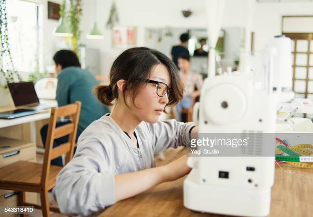 Young woman designer preparing a sewing machine