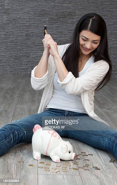Young woman destroying piggy bank with hammer