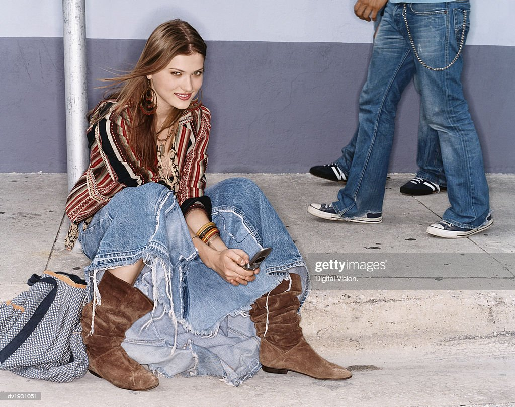 Young Woman Dialing Her Mobile Phone Sitting on the Pavement : Stock Photo
