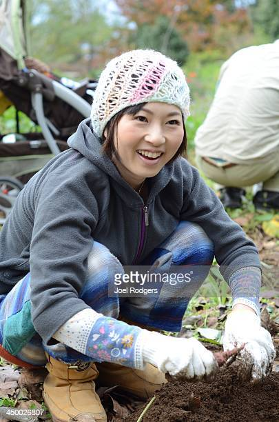 Young woman digging for sweet potatoes