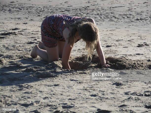 Young Woman Digging Sand At Beach