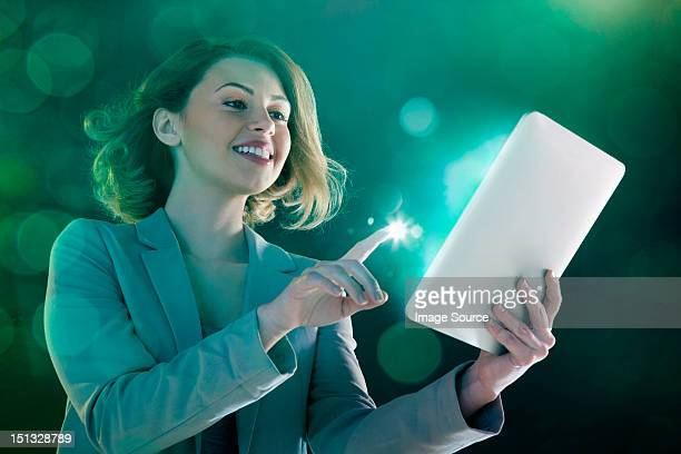 Young woman digital tablet and light on finger