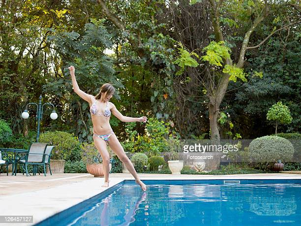 Young woman dipping toe in swimming pool