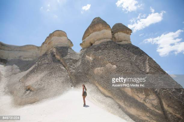 Young woman discovers rock formations in desert environment