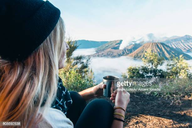 Young woman discovers volcanic landscape, from tent