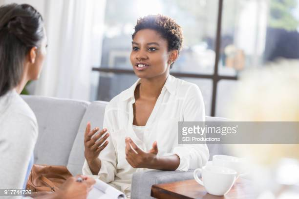 young woman discusses issues with female therapist - psychologist stock photos and pictures