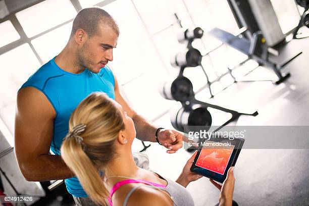 Young woman discussing workout progress with fitness instructor