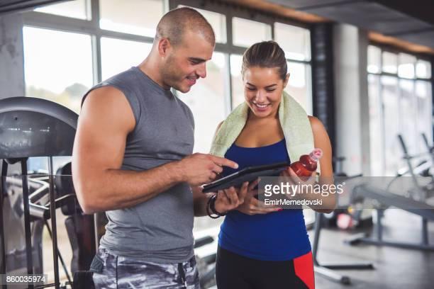 junge frau mit fitness-instruktor training fortschritte zu diskutieren - sporttraining stock-fotos und bilder