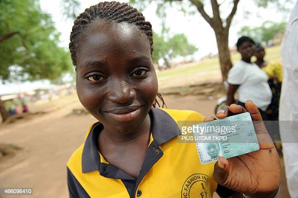 A young woman displays her Permanent Voter Cards at Shimawa a rural town in southwestern Nigeria on March 13 2015 The Independent National Electoral...