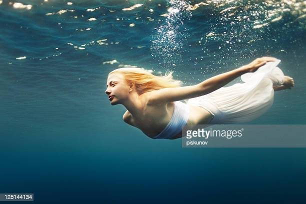 young woman dive into deep water - mermaid stock photos and pictures