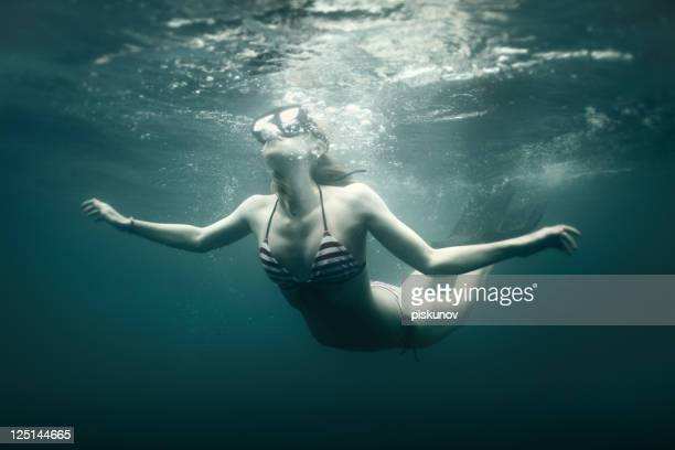 Young woman dive into deep water