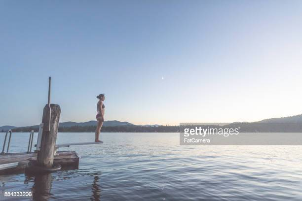Young woman dives into a lake off pier at dusk