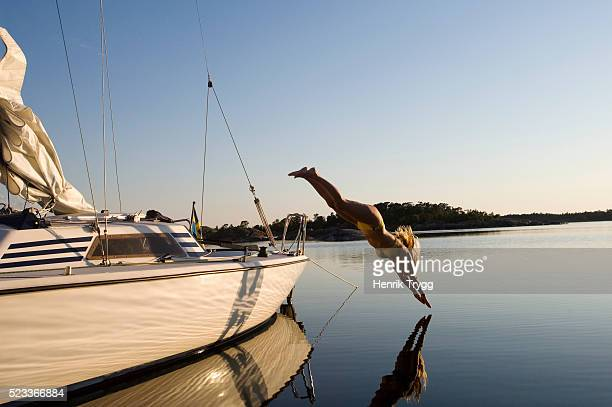 young woman diving from a boat - archipelago stock pictures, royalty-free photos & images