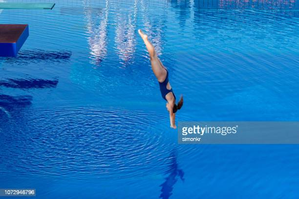 young woman diving in swimming pool - diving board stock pictures, royalty-free photos & images
