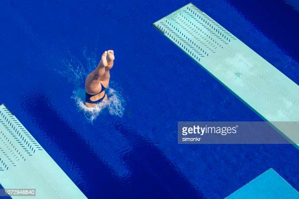 young woman diving in swimming pool - diving into water stock photos and pictures