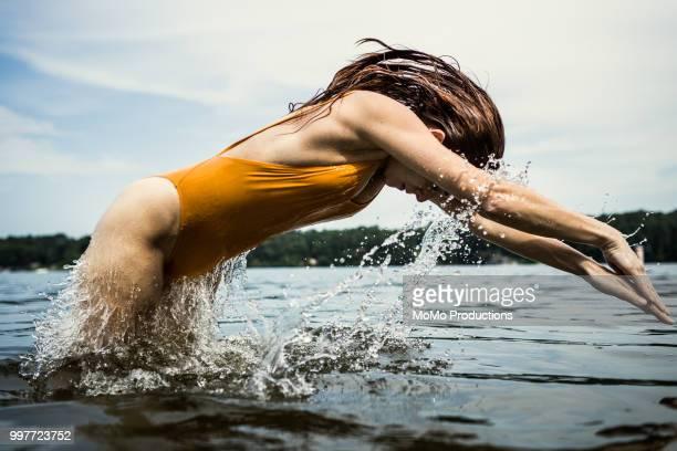 young woman diving water at lake