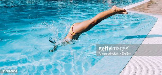 young woman diving into pool - taking the plunge stock photos and pictures