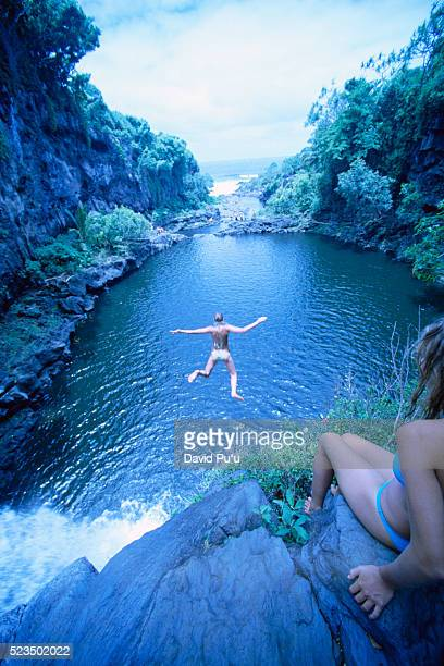 Young Woman Diving off of Cliff