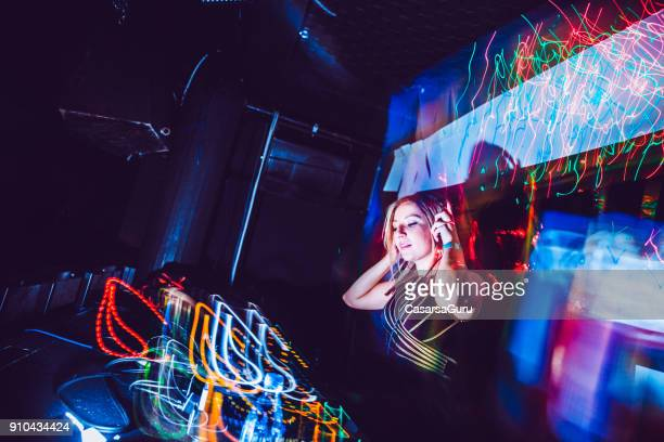 Young Woman DJ Listening  On Headphones while Performing