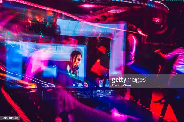 young woman dj performing in a nightclub - club dj stock pictures, royalty-free photos & images