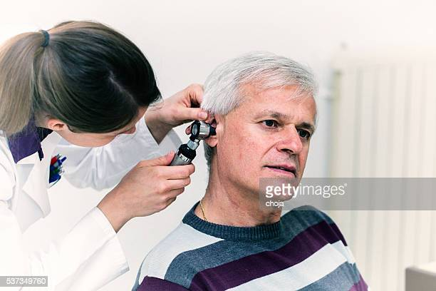 Young woman doctor checking patients ear with otoscope