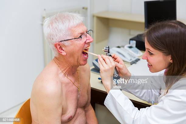 Young woman doctor checking patients oral cavity with otoscope