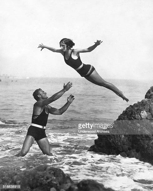 A young woman does a high dive off a rock into the arms of a Los Angeles life guard in three feet of water Los Angeles California mid 1920s