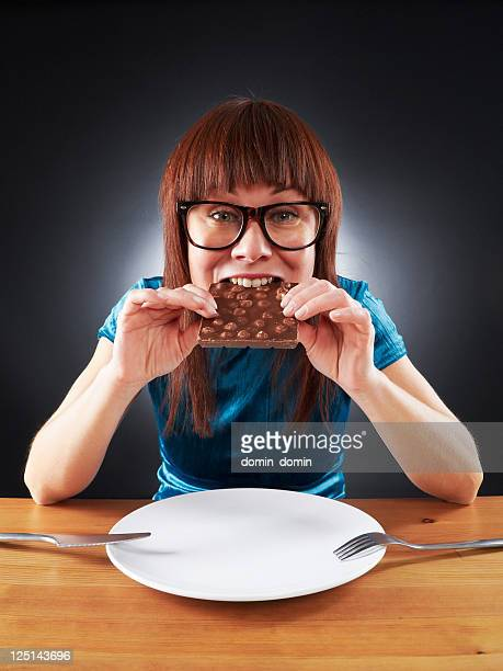Young woman does not count calories, eating chocolate bar