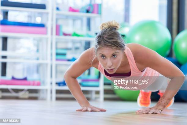 Young woman does push ups in the gym