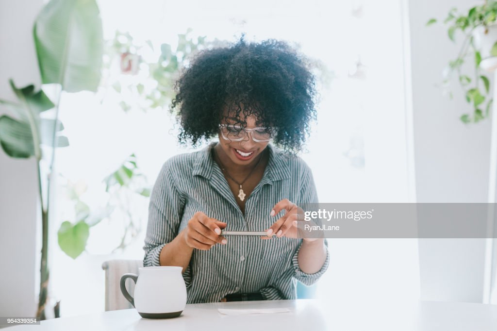 A Young Woman Does Remote Deposit Capture of Check : Stock Photo