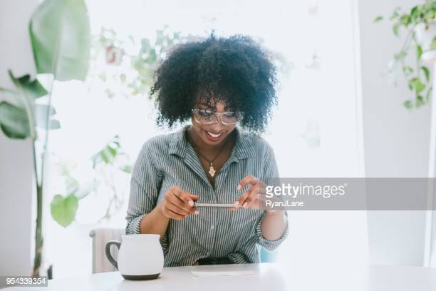 a young woman does remote deposit capture of check - financial bill stock pictures, royalty-free photos & images