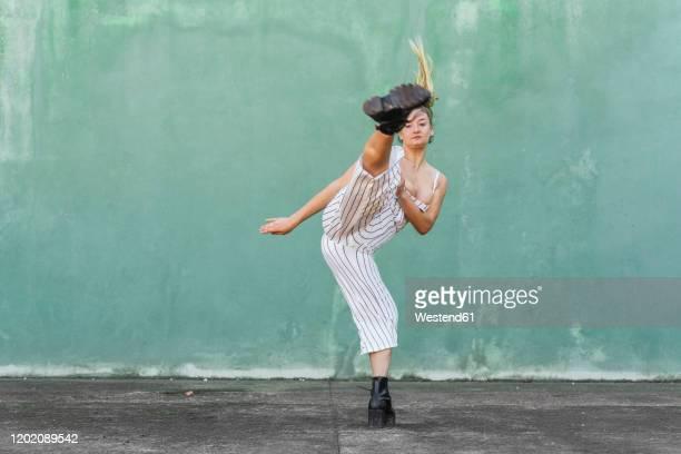 young woman doing a high kick in front of green wall - verteidigen stock-fotos und bilder