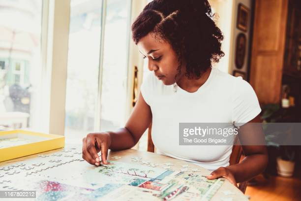 Young woman doing a puzzle at home