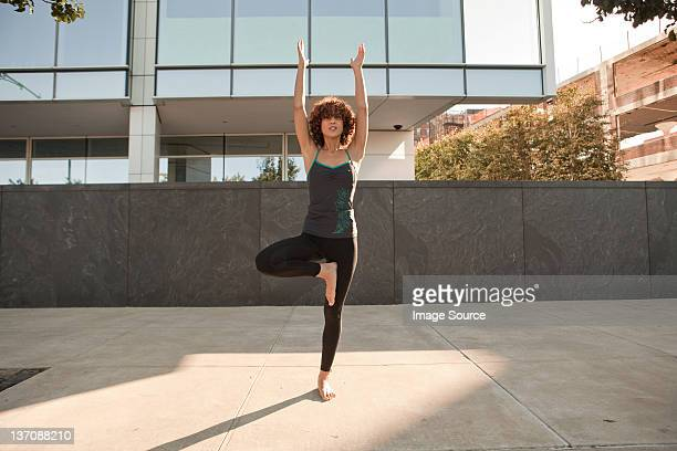 Young woman doing a tree pose on the pavement