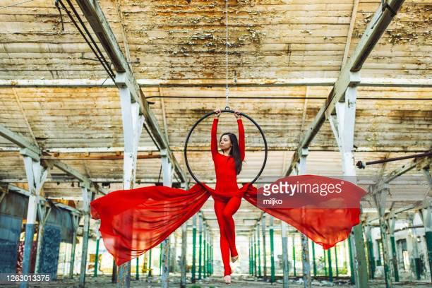 放棄された建物で空中フープダンスをしている若い女性 - 空中曲芸師 ストックフォトと画像