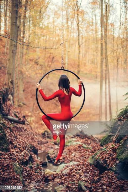 屋外で空中フープダンスをしている若い女性 - 空中曲芸師 ストックフォトと画像