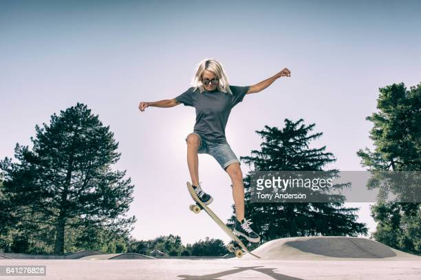 young woman doing an ollie at skatepark - ollie pictures stock pictures, royalty-free photos & images