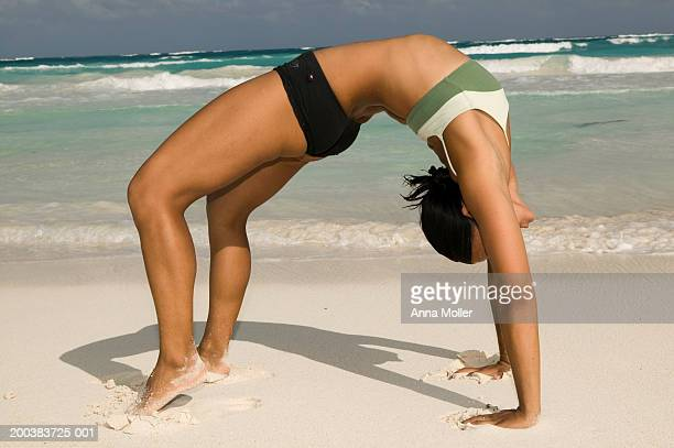 Young woman doing backbend on beach, side view