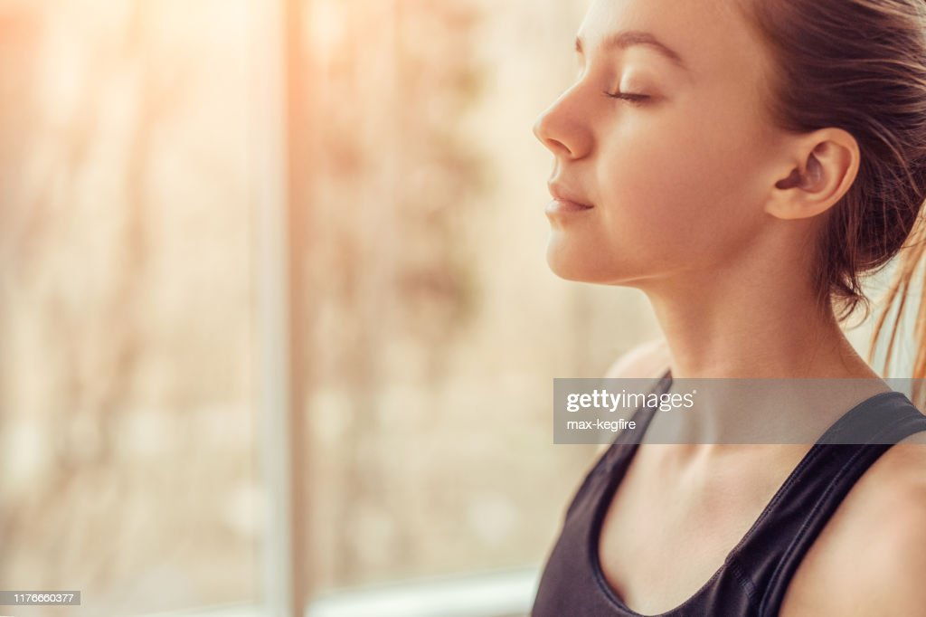 Young woman doing breathing exercise : Stock Photo