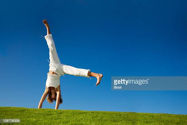 Young woman doing cartwheel in a grassy field
